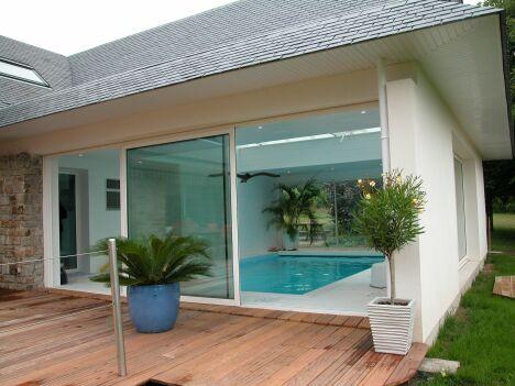 Piscine intérieure entourée de carrelage blanc, avec baie vitrée et terrasse en bois