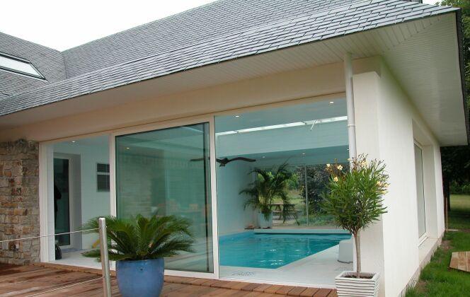 Piscine intérieure entourée de carrelage blanc, avec baie vitrée et terrasse en bois © L'Esprit Piscine