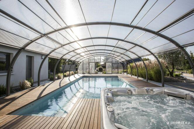 Photographie :  Piscine enterrée et spa, abri de piscine haut, pour Abrisud.© Abrisud - Fred Pieau