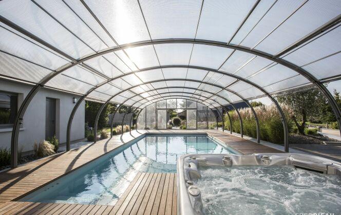 Photographie :  Piscine enterrée et spa, abri de piscine haut, pour Abrisud. © Abrisud - Fred Pieau
