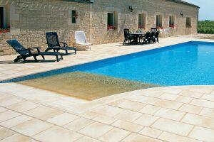 Prolongement de la terrasse, la plage de pierres claires s'immerge dans la piscine