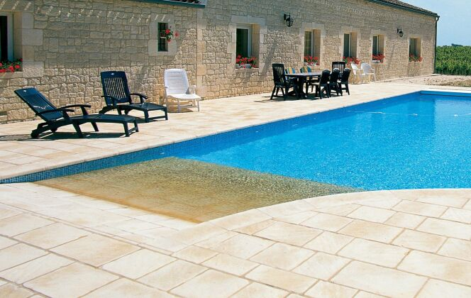 Prolongement de la terrasse, la plage de pierres claires s'immerge dans la piscine © L'Esprit Piscine