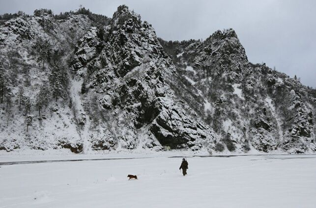 Un homme promène son chien au bord du fleuve
