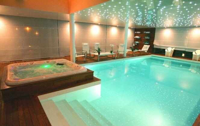 Piscine intérieure avec spa & hammam, plages bois verni et ciel étoilé © L'Esprit piscine