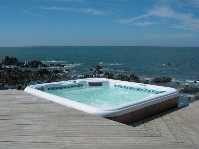 Spa extérieur avec solarium de bois et vue imprenable sur la mer.