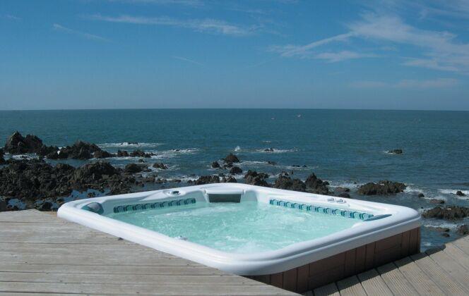 Spa extérieur avec solarium de bois et vue imprenable sur la mer. © L'Esprit Piscine