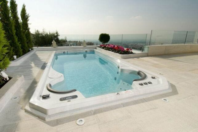 Spa de nage Acrylique entouré d'une plage de pierres claires et de barrières en verre