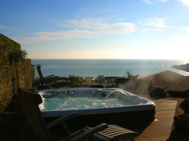Spa extérieur avec solarium de bois, vue sur mer et lumière de fin de journée.