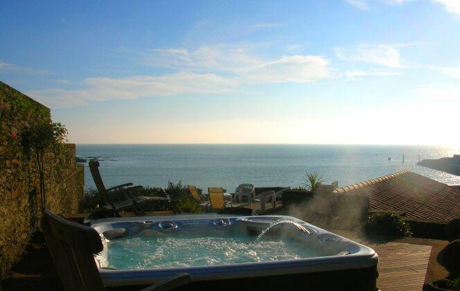 Spa extérieur avec solarium de bois, vue sur mer et lumière de fin de journée. © L'Esprit Piscine