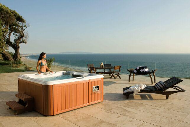 Spa extérieur aspect bois clair, cadre idyllique en bord de mer.