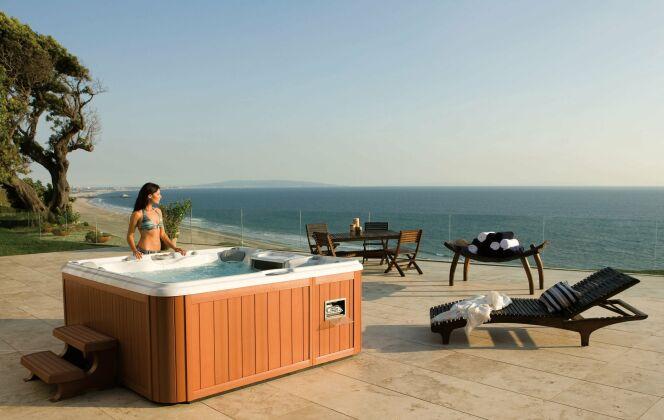 Spa extérieur aspect bois clair, cadre idyllique en bord de mer. © Sundance Spas
