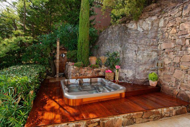 Spa extérieur avec bois chaleureux, vieilles pierres et végétation luxuriante.