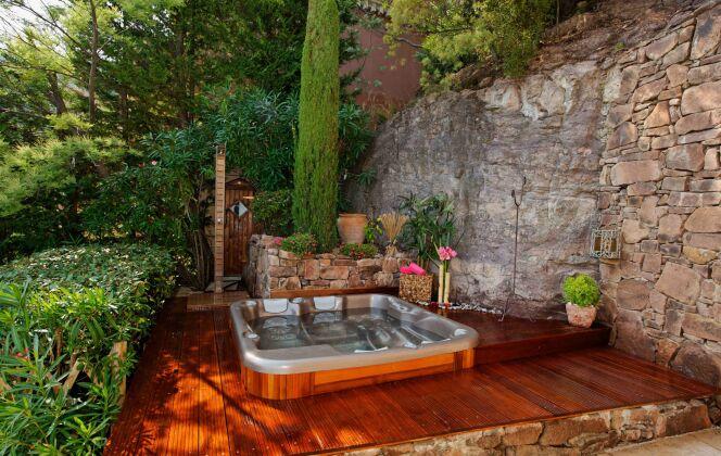 Spa extérieur avec bois chaleureux, vieilles pierres et végétation luxuriante. © L'Esprit Piscine
