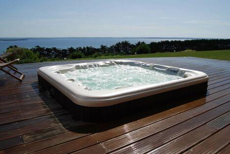 """Spa extérieur avec grand solarium de bois et vue sur mer.<span class=""""normal italic petit"""">© L'Esprit Piscine</span>"""