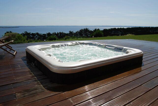 Spa extérieur avec grand solarium de bois et vue sur mer.