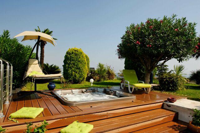 Spa extérieur avec solarium de bois, mobilier de jardin coloré et végétation luxuriante : une ambiance chaleureuse et conviviale.