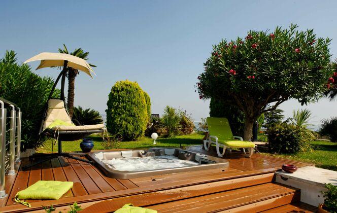 Spa extérieur avec solarium de bois, mobilier de jardin coloré et végétation luxuriante : une ambiance chaleureuse et conviviale. © L'Esprit Piscine