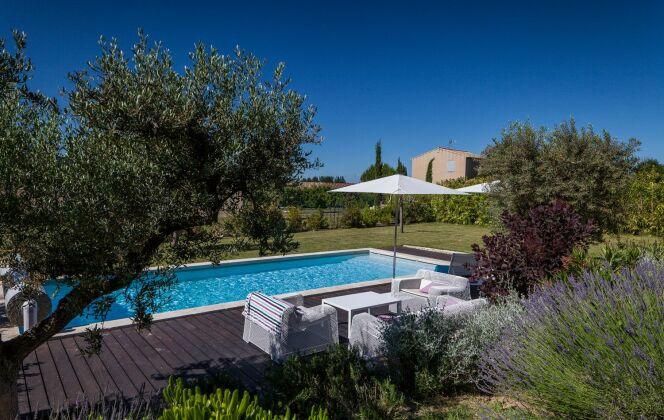 Terrasse avec piscine et aménagement de jardin avec plantes. © Piscines Magiline