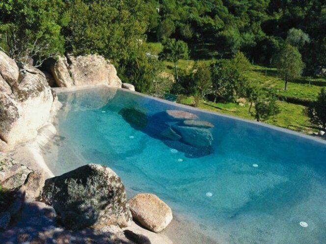 """Une piscine avec faux rochers décoratifs <span class=""""normal italic petit"""">© piscinesbiodesign.fr</span>"""