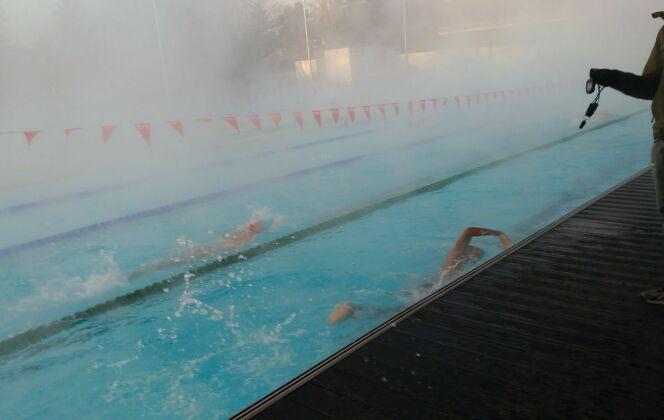 Veste chaude, bonnet sur la tête et chronomètre en main, les entraîneurs surveillent les temps de leurs nageurs. DR